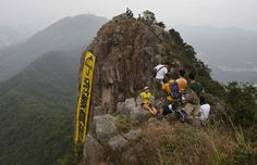 """Hikers take pictures of the yellow banner with the words reading: """"I want genuine universal suffrage"""" in Chinese and âUmbrella Movementâ in English hanging on the face of Lion Rock mountain in Hong Kong Thursday, Oct. 23, 2014. Democracy activists hung the banner on the mountain in support of the protest movement in which thousands of demonstrators have camped out on the streets of the southern Chinese financial center for nearly a month to press their demands for greater democracy."""