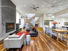 Dining-living living room using grey colours with floorboards & fireplace - Living Area photo 8475853