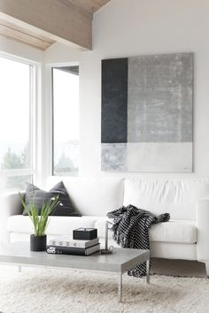 The white living room of Nina Holst, the blogger behind Stylizimo, is grounded with black accents and a monochromatic, color block painting by the blogger herself.