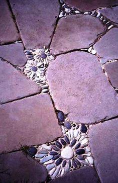 mosaik im garten große Steinplatten und kleine Blumen