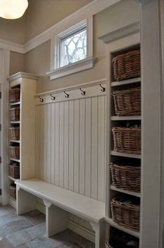 Love this mudroom foyer idea for keeping everything neat and decluttered - the white wall is gorgeous and the baskets make it easy to stay organized and neat.