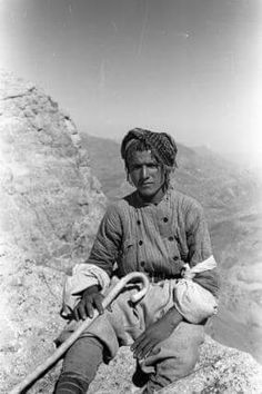 Portrait of a Kurdish Man, sitting on Rocks on Mount Hendren, holding a Stick in his right Hand, with Mountains in the Distance, near Rawanduz, 1949.