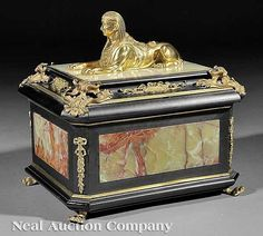A Continental Onyx and Gilt Bronze-Mounted and Ebonized Coffer, the hinged cover with rocaille mounts and surmounted by a sphinx, beribboned floral mounts on canted corners, gilt bronze paw feet, height 15 in., width 15 1/2 in., depth 12 in