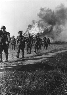 German soldiers march past a burning home. Ukraine. October 1941.