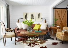 White barn-style shiplap siding gives the one-dimensional living room texture. While the coffee table with industrial springs and barn doors are quirky focal points.