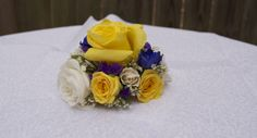 Bright and bold corsage of yellow roses, cobalt blue delphinium and royal purple statice.