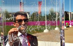 Lord Sebastian Coe signs his name on the Peace Wall inside the main entrance to the Olympic Athletes Village, before the official opening of the Village, in Stratford, east London