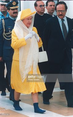 Queen Elizabeth II, wears a scarf over her hat to cover her hair and walks in socks without shoes as a sign of respect as she visits the Shah Faisal Mosque on October 07, 1997 in Islamabad, Pakistan.