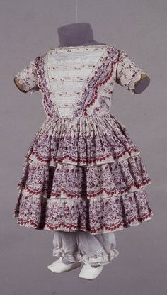 1840 girl's printed muslin dress.  White with mauve spots and pattern in mauves and reds with heavier boarder pattern.