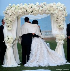 White #chuppah  covered with white hydrangea, roses, and billowing silk chiffon.