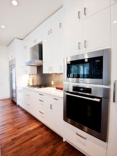 A simple kitchen with stacked, eye level ovens, exhaust ventilator and fridge.