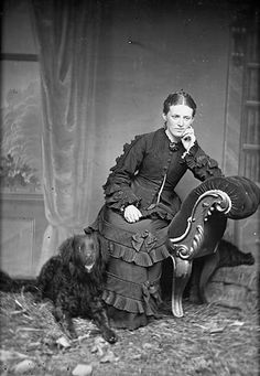 A Victorian woman in a beautiful, elaborately embellished dress posing with a cute curly haired dog.