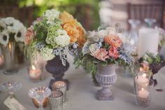 Small different color flowers and miniature glass votive candles as table centerpieces.