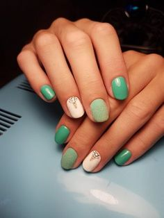 This is white and green nail art with rhinestones.