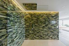 Vis-à-vis vom Whirlpool befindet sich die begehbare Dusche mit grossformatigem Natursteinboden und grünen Natursteinwänden. Weitere interessante Naturstein Badezimmer und Wellnessbereiche finden Sie auf www.stonegroup.ch.