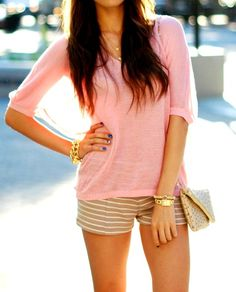 Relaxed summer outfit, pink top with beige striped shorts and golden accessories.