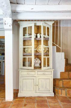 En la casa rehabilitada de Villaseca, junto a la escalera que conduce a la planta de los dormitorios una hermosa alacena decapada en blanco con vajilla de El Almacén de la Loza.