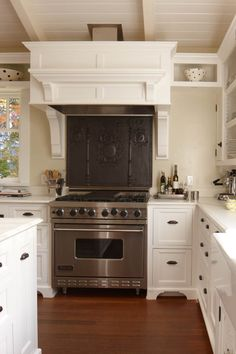White kitchen with Viking stove and great hood, tile and hardware
