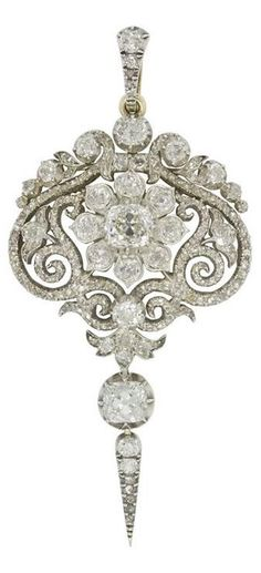 A fine early Victorian diamond pendant, the pendant delicately set with a central floral cluster, to the centre of an ornate openwork scroll-design plaque, encrusted throughout with old brilliant- and rose-cut diamonds, with old brilliant-cut diamond drop, estimated to weigh a total of 6.3 carats, all cutdown silver collet-set to a yellow gold mount, with convertible brooch fitting, gross weight 16 grams, circa 1840.