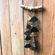 A waterfall of grey brown clay fans, attached to a branch with flax cord. Brown And Grey, Wind Chimes, Cord, Waterfall, Ornament, Artisan, Fans, Etsy Shop, Ceramics