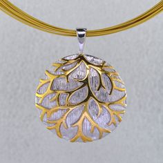 Circular Disk in sterling silver etched on the inside with yellow gold plated branch motif.