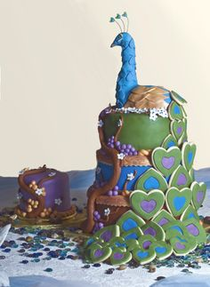 Peacock is hand-sculpted and fully edible, made of cereal treats, sugarpaste, and fondant. The cookie tail is orange spice sugar cookies covered in fondant. A grape vine climbs up alongside the tiers and a separate cake for the bride and groom sits beside it.