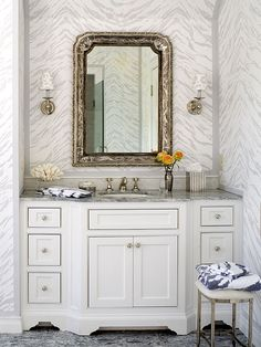 The animal motif carries into the bathroom, with leopard-spot sconce shades adding a playful contrast to the tiger-stripe walls. A graceful Louis Philippe-style antique mirror balances the modernity of the suite's design. (Photo: Emily Minton Redfield)