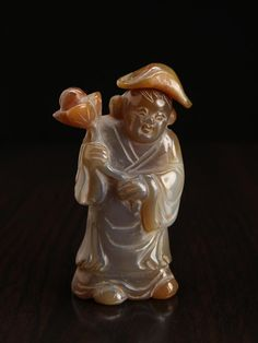 """Chinese Carved Agate Snuff Bottle -  Carved to depict a three-dimensional standing, robed boy figure holding a lotus. 3.125"""" H x 1.5"""" W"""