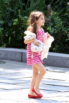 Suri Cruise's Best Fashion Moments, So Far At only 7, this little lady has donned more darling outfits than most of us could count in kindergarten. . . . Stripes - Suri toted her things around wearing an easy striped day dress and standout red shoes.  So simple but so cute!