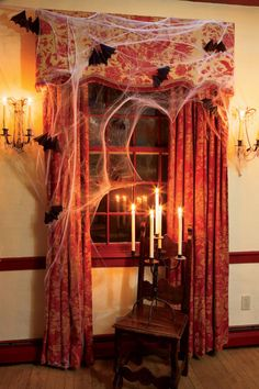 Use candlelight to create dark shadows in the corners. Here, the ghostly white tapers in a flea market candelabra enhance the creepiness of cobwebs and flying bats.
