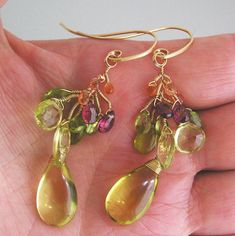 ...........both cheerful and elegant.......... Dazzling gemstones of lemon quartz, orange sapphire, peridot, pink tourmaline, and vesuvianite are wire wrapped to form full vines. Tipped with smooth lemon quartz briolettes (20mm). Hand fabricated 14k gold filled 20 gauge ear hooks.