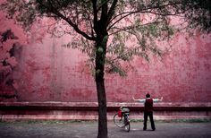 A man does Tai Chi in Beijing China He is facing one of the walls of the Forbidden City