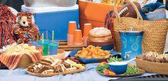 Baskets, colorful napkins on wood serving pieces, orange or blue drink in plastic dispenser...