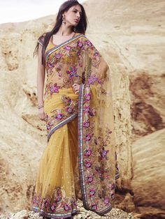 Look classy in this gorgeous yellow nett designer saree. This is definitely worth buying as it will make you glamorous. The Saree has heavy multi colored floral applic work and contrast zari border which enhances the beauty of the sari. (Slight variation in color is possible)