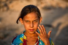 """A young Syrian girl living in a refugee camp in Lebanon - """"I photographed the green-eyed girl after noticing the word """"love"""" written out on her hand in English and Arabic. When I asked further about the girl, I found out she had lost her whole family only a few days ago. So it struck me how she could stand there, her eyes shining and think of love."""" ~photographer Mimo"""