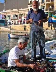 Fishermen cleaning their fishing nets in Spinola Bay, St Julians, Malta.
