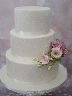 Bruidstaart kanten bewerking en suikerwerk boeket van lisianthus en rozen.