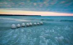 Cotton Tops by wendy chapman on Capture Wisconsin // Can you guess?  These cotton balls are actually the ice covered footings of a long gone pier. They are now completely covered undered the ice bergs that have taken over the shoreline.