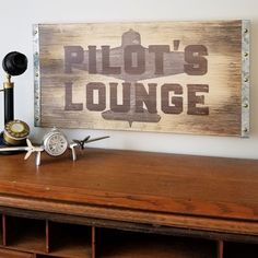 Distressed wood panel is trimmed in metal with rivets and features tonal aircraft behind Pilot's Lounge lettering. Looks great in any aviation themed decor, whether in home, office or bar. Aviation Theme, Aviation Art, Airplane Decor, Nostalgic Art, Calming Colors, Home Office Furniture, Building Furniture, Wood Furniture, Furniture Ideas