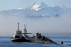 The ballistic missile submarine USS Henry M. Jackson transits past the Olympic Mountains as it prepares to conduct sea trials in Bangor, Wash
