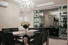 Na sala de jantar, a cor preta se destaca na marcenaria e nos vidros, tornando o ambiente sofisticado e elegante. A escolha valoriza o lustre de cristais transparentes que ilumina de forma muito sutil o teto de gesso e, ao mesmo tempo, proporciona iluminação adequada para servir um bom jantar.
