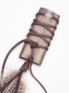 Metallic Leather Hair Wrap | Decorate your 'do with this metallic leather hair wrap featuring a dangling feather detail.