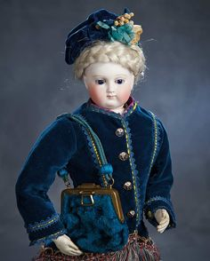 attributed to Barrois,circa 1860. Value Points: beautiful early poupee with sturdy original body is wearing beautiful antique costume comprising blue velvet jacket with silk fringe and fancy buttons,matching blue velvet cap,gold silk skirt with silk ribbon appliques,undergarments,fancy leather boots with Huret-like soles,and carrying beautiful blue velvet purse with blue cord and beading.