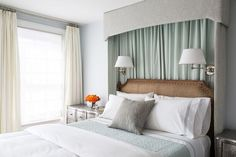 Sophisticated bedroom features a gray valance paired with green curtains placed above and behind a ...