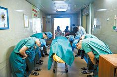 Chinese doctors bowing down to an 11 year old boy with brain cancer who saved several lives by donating his organs