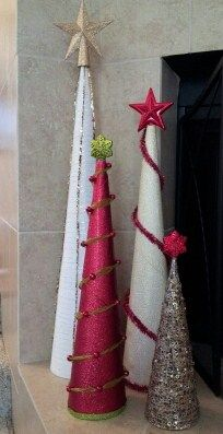 DIY - Christmas Cone Trees. YouTube showed me how to make 3 cones out of 2 posterboards - $2. I used white mesh ribbon, red glitter wrapping paper & gold glittered organza to wrap each cone. $6 to get the star & snowflake toppers & other dec's. Also bought a small gold tree at Tues Morning & put a little snowflake on top to finish off the set. Glue gun for all. So easy & affordable. These  will be beautiful on a snow blanket with my little deer, on the fireplace, & a wreath hanging above…