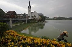 A worker spray water on plants at an European-style houses in Hallstatt See, a replica of the Austrian town of Hallstatt, in Boluo county, Huizhou city, south China's Guangdong province Saturday, June 2, 2012. A group of Austrians whose scenic mountain village has been copied down to the statues by a Chinese developer attended Saturday's opening in China for the high-end residential project but were still miffed about how the company did it. The original is a centuries-old village of 900…
