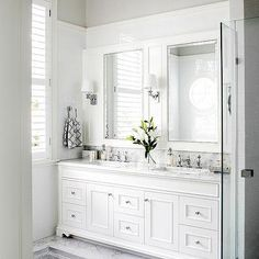 White vanity with double sinks. This lovely bathroom has such a soft feel to it with the wall sconces and the white-framed mirrors. Shaker style cabinets with nickel pulls finish off this bathroom.