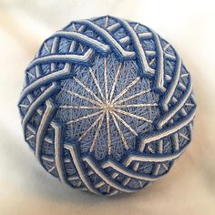 3.5-diameter temari ball wrapped in light blue thread and stitched with overlapping diamonds in graded shades of blue and white, forming a complex, swirling mandala, with silver metallic accents