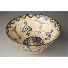 Bowl; early 13th c, Iran  Bowl of white fritware with decoration painted in blue and black under a clear glaze. Outside are pairs of blue stripes alternating with formal stems in black. Inside is a border of semi-circular blue and black panels containing formal leaves and a series of radial devices. In the centre is a circular medallion containing a bird-woman.  Medium: Fritware with underglaze painting